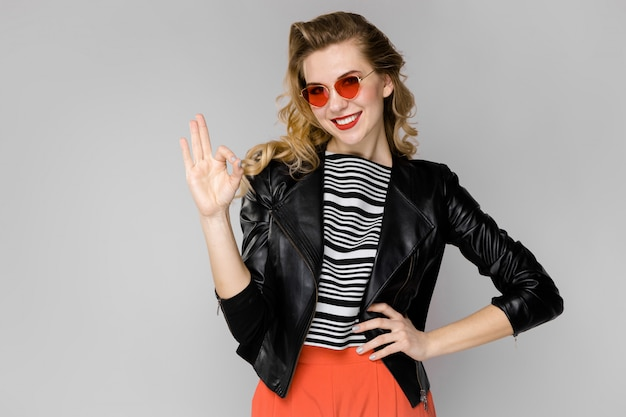 Attractive young blonde girl in striped blouse and leather jacket smiling in sunglasses with hands on waist standing