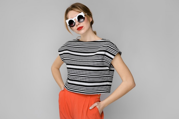 Attractive young blonde girl in striped blouse smiling in sunglasses with hands on waist on gray