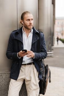 Привлекательный молодой светловолосый мужчина в формальной одежде разговаривает через наушники, держа мобильный телефон, стоя на улице на улице города