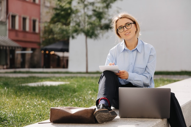 眼鏡、青いシャツ、黒のジーンズで魅力的な若いブロンドの屋外でメモを書きます。開いたラップトップと脇に座って幸せな女性。