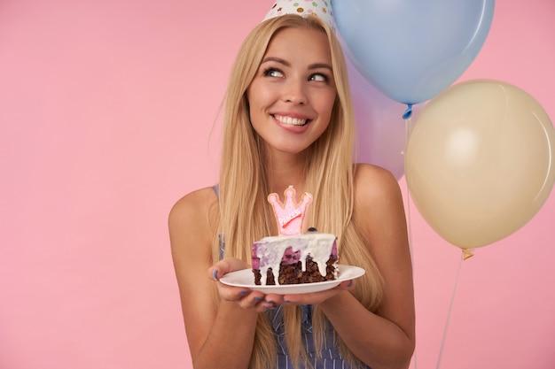 Attraente giovane signora bionda con un pezzo di torta nelle sue mani guardando da parte sognante con un ampio sorriso felice, indossando abiti estivi blu e cappello a cono mentre in piedi su sfondo rosa
