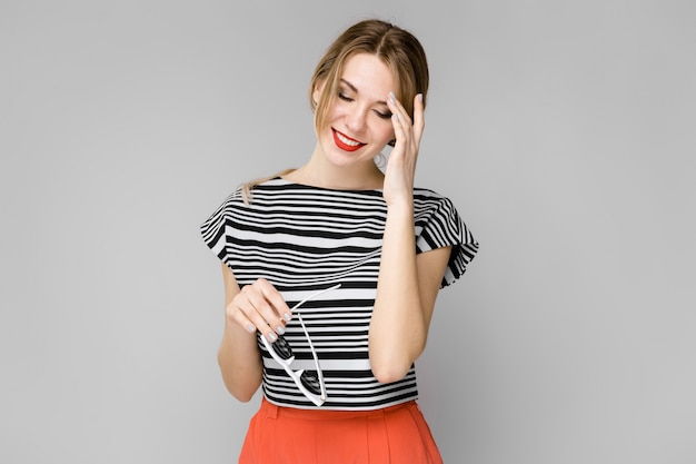 Attractive young blonde shy girl in striped blouse smiling holding her glasses standing on gray