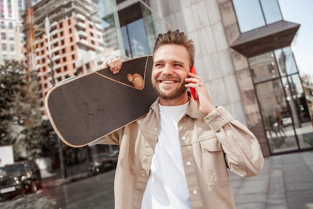 ガラスの建物の間に立っている街の通りで肩にスケートボードを保持している魅力的な若い金髪の笑顔の男。デニムの服を着ています。スポーティでスタイリッシュなスケートボーダーが携帯電話のラウフで語ります。
