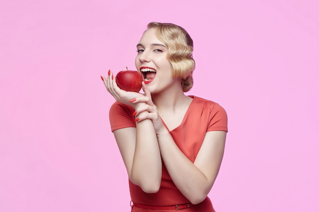 レトロな髪型の魅力的な若いブロンドは、赤いリンゴを噛もうとしています
