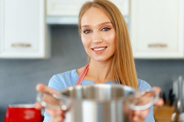 Привлекательная молодая блондинка проверяет приготовленную пищу, крупным планом