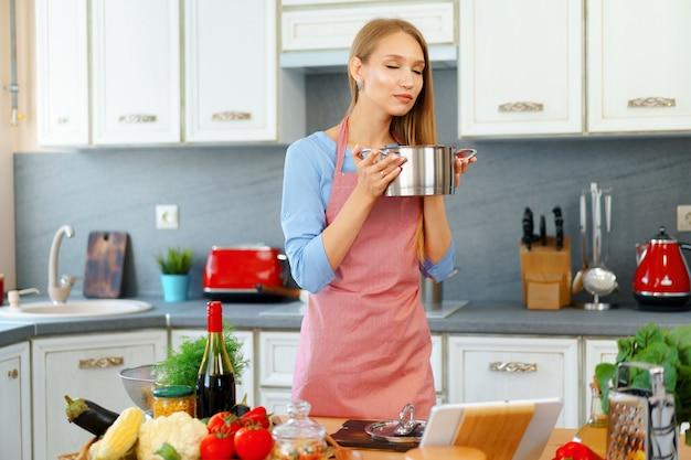 Привлекательная молодая блондинка проверяет приготовленную пищу