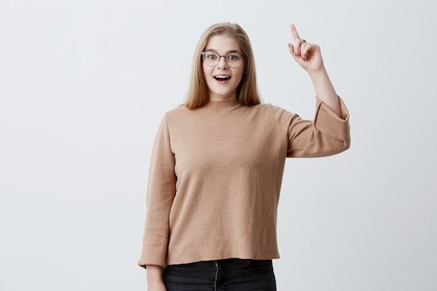 Attractive young blonde woman of european appearance looking  and raising index finger, smiling, having bright idea or interesting thought, standing isolated against blank studio wall