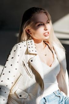 청바지에 유행 여름 재킷에 흰색 세련된 티셔츠에 매력적인 젊은 금발의 여자는 봄 날에 밝은 햇살을 즐깁니다