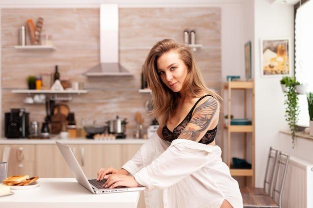 ノートパソコンでタイピングランジェリーの魅力的な若いブロンドの女性。魅惑的な下着の笑顔に身を包んだキッチンに座ってpcに入れ墨を入力して魅力的なブロンドの女性