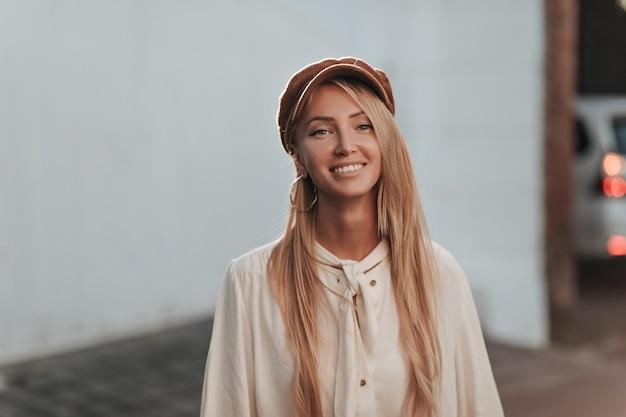 Attraente giovane donna bionda in camicetta leggera di cotone alla moda e berretto marrone alla moda di velluto sorride e guarda in avanti all'esterno