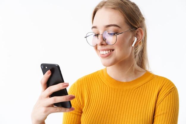 Привлекательная молодая блондинка женщина в свитере стоя изолирована над белой стеной, носить беспроводные наушники, показывая мобильный телефон