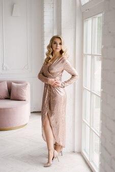 Привлекательная молодая блондинка с вьющимися волосами и макияжем в расшитом блестками платье в ярком интерьере дома-студии