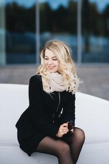 예쁜 화장과 매력적인 젊은 금발의 여자, 캐주얼 거리 착용, 건물의 타일 벽 앞에 흰색 플라스틱 소파에 앉아
