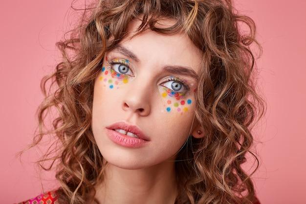 Attraente giovane femmina dagli occhi azzurri con acconciatura festosa e trucco in piedi, guardando con gli occhi spalancati e la bocca socchiusa