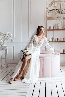 An attractive young bride in a beautiful boho wedding dress posing with a bouquet in a bright room.
