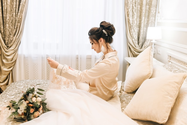 Attractive young bride holding a wedding dress. morning bride in a luxury hotel