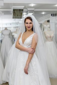モダンなサロンでウェディングドレスの魅力的な若い花嫁