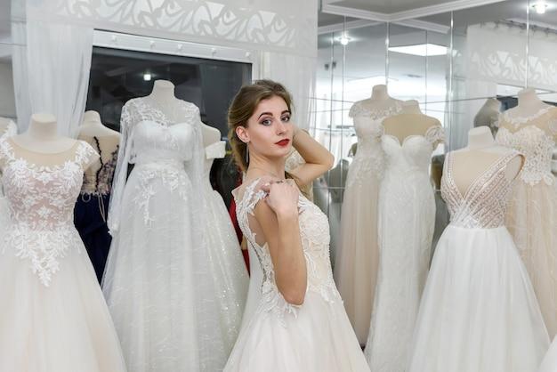 魅力的な若い花嫁は結婚式のサロンで笑っています