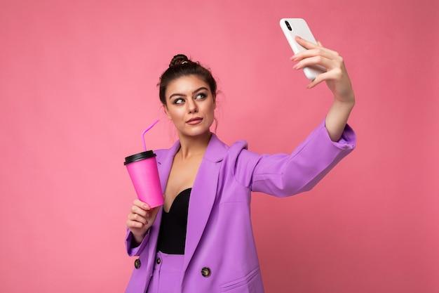Привлекательная молодая брюнетка женщина в модном фиолетовом костюме на розовом