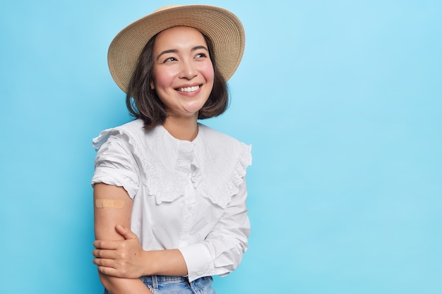 Attractive young brunette asian woman with vaccinated arm wears stylish hat white blouse rolls out sleeve shows bare shoulder with adhesive plaster isolated over blue wall