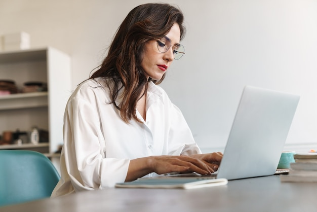Attractive young brunette businesswoman sitting at the cafe table with laptop computer indoors
