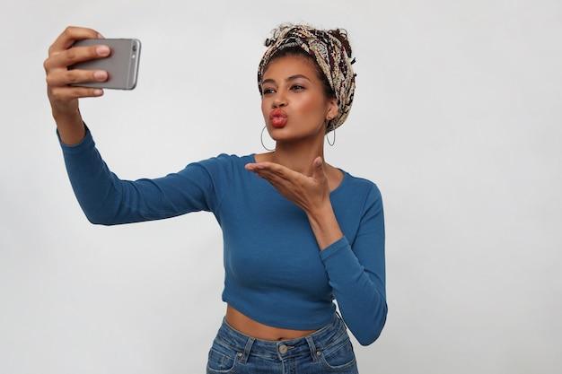魅力的な若いブルネットの暗い肌の女性は、白い背景の上に立って、携帯電話で自分の写真を撮っている間、カメラでエアキスを送信します
