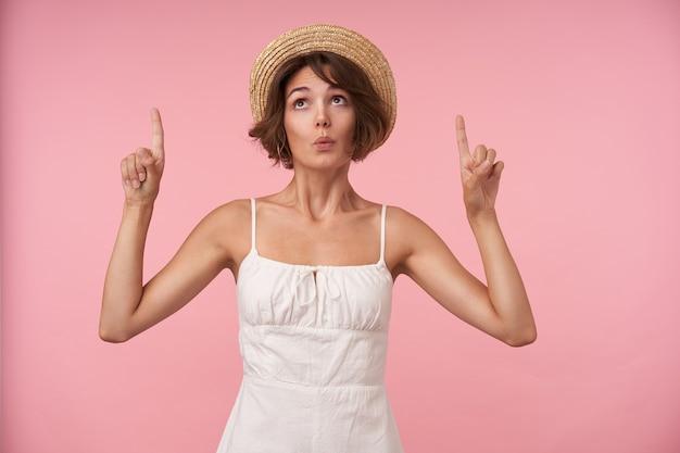 Attraente giovane donna bruna con acconciatura casual guardando verso l'alto con le sopracciglia alzate e alzando gli indici, piegando le labbra mentre si trova in piedi
