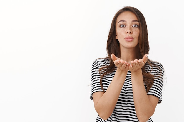 Attractive young brunette girl in striped t-shirt blowing air kiss at front, pouting give mwah hold hands near folded lips, gaze camera gently