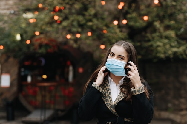 通りでポーズをとる医療マスクの魅力的な若いブルネット。パンデミックの時期に一人で屋外を歩く暖かい服を着たきれいな女性。