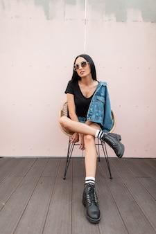 Привлекательная молодая брюнетка женщина в футболке в джинсовой куртке в солнечных очках в кожаных черных сапогах сидит на стуле у стены на улице в городе. модная хипстерская девушка на открытом воздухе. осенний стиль