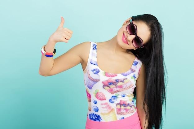 Привлекательная молодая брюнетка женщина в розовой майке на синем