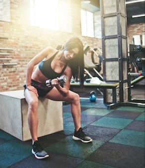 スポーツウェアの魅力的な若いブルネットの女性は、ジムの木製の箱に片手で座って上腕二頭筋のダンベルを持ち上げて運動を集中させます