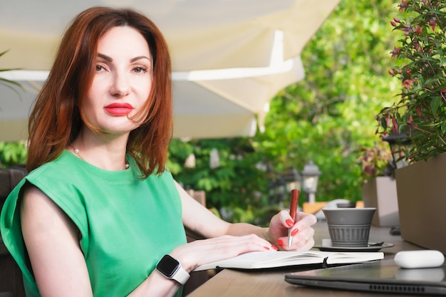 Attractive young brunette woman sits in a cafe at a table with laptop cup of coffee and makes notes