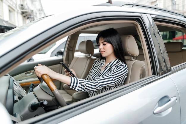集中して彼女の電話で車のテキストメッセージのホイールの後ろに座っている魅力的な若いブルネットの女性