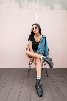 Attractive young brunette woman in a t-shirt in a denim jacket in sunglasses in leather black boots sits on a chair near wall on the street in the city. fashionable hipster girl outdoors. autumn style