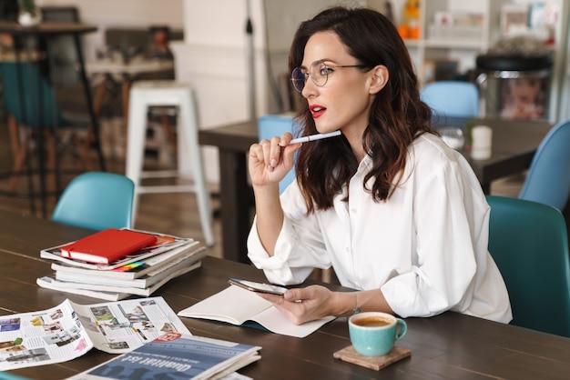 Привлекательная молодая брюнетка женщина с помощью мобильного телефона во время учебы в кафе в помещении