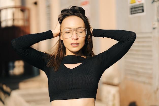 路上でポーズをとる黒いトップと透明なメガネを身に着けている魅力的な若いブルネットの女性。メガネで陽気な白人女性のクローズアップの肖像画