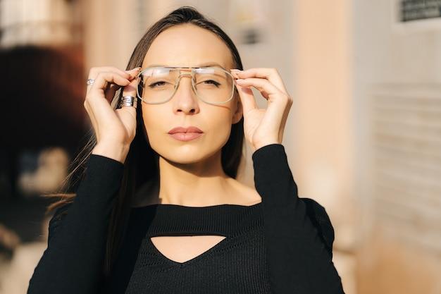 路上でポーズをとる黒いトップと透明なメガネを身に着けている魅力的な若いブルネットの女性。