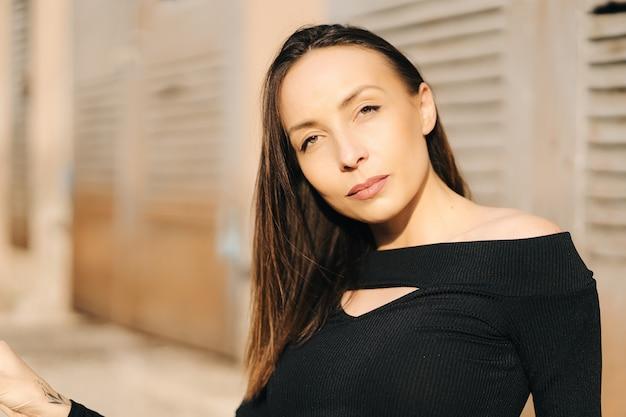 通りでポーズをとって黒いトップを着ている魅力的な若いブルネットの女性。