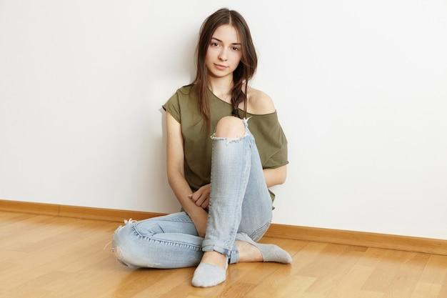 トレンディなボロボロになったジーンズとオープンショルダーのトップを着て魅力的な若いブルネットの女性
