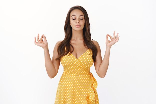 예쁜 노란색 여름 드레스에 주근깨가 있는 매력적인 젊은 갈색 머리 여성, 명상, 호흡 연습 요가를 사용하여 진정, 선 제스처를 보여줍니다