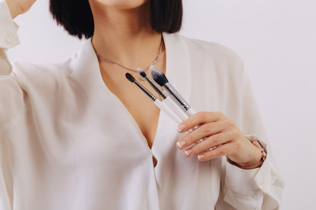 Attractive young business girl with makeup brushes posing on plain wall. concept of makeup and cosmetics.