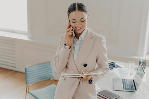 Привлекательная молодая бизнес-леди разговаривает по мобильному телефону с боссом о рабочих вопросах и смотрит в блокнот, стоя возле рабочего стола с ноутбуком в светлом стильном офисе