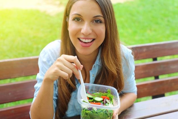 Привлекательная молодая бизнес-леди обедает, сидя в городском парке, глядя на камеру.