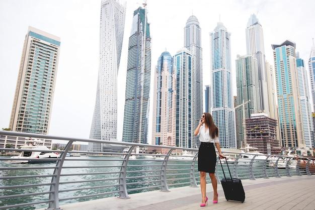 壮大な街でスーツケースを引っ張って魅力的な若いビジネス女性。美しい街並みのパノラマビュー。