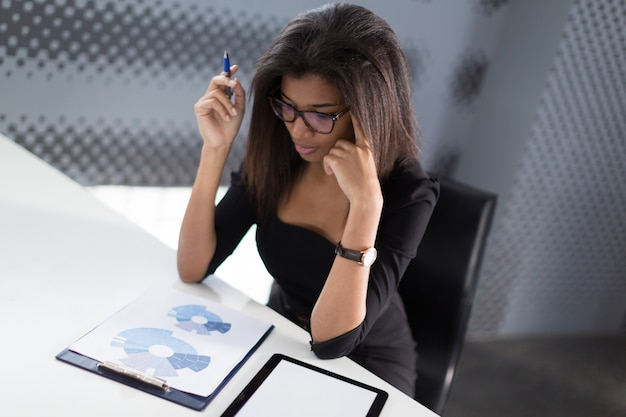 Attractive young businesslady in black strong suite sit at the office table