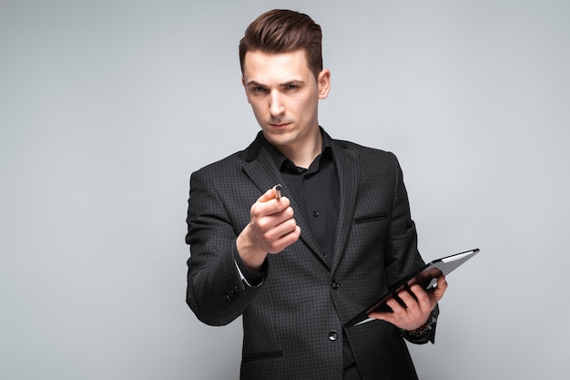 Attractive young businessman in black jacket, costly watch and black shirt hold tablet