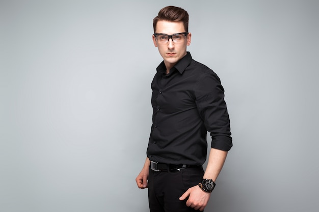 Attractive young businessman in costly watch, glasses and black shirt