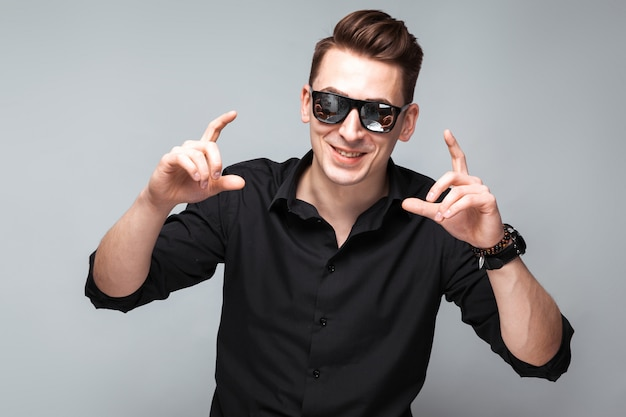 Attractive young businessman in costly watch, sunglasses and black shirt