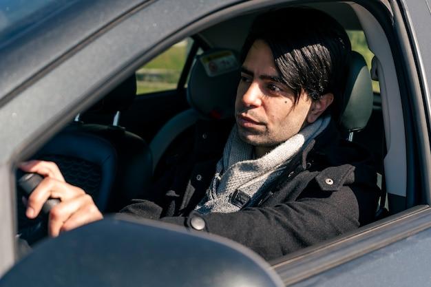차를 운전하는 매력적인 젊은 사업가. 교통 및 토지 통신 개념입니다.